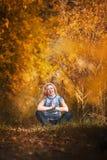 做瑜伽的美丽的妇女户外在黄色叶子 库存照片