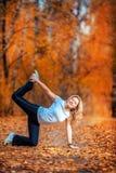 做瑜伽的美丽的妇女户外在黄色叶子 图库摄影