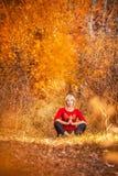 做瑜伽的美丽的妇女户外在黄色叶子 免版税库存图片