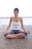 做瑜伽的美丽的少妇在家行使 免版税库存图片