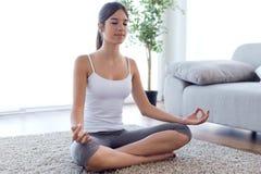 做瑜伽的美丽的少妇在家行使 图库摄影