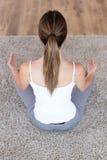 做瑜伽的美丽的少妇在家行使 免版税库存照片