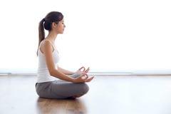 做瑜伽的美丽的少妇在家行使 库存图片