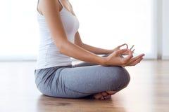 做瑜伽的美丽的少妇在家行使 免版税图库摄影