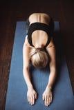 做瑜伽的美丽的年轻女运动员顶视图行使 免版税库存照片