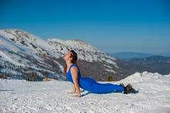 做瑜伽的蓝色成套装备的女孩在w的一座山顶部 库存图片
