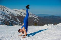 做瑜伽的蓝色成套装备的女孩在w的一座山顶部 免版税库存照片