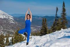 做瑜伽的蓝色成套装备的女孩在w的一座山顶部 免版税库存图片
