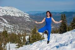 做瑜伽的蓝色成套装备的女孩在w的一座山顶部 库存照片