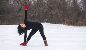 做瑜伽的西班牙妇女在冬天安置外部 库存照片