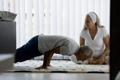 做瑜伽的资深夫妇 免版税库存照片