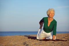 做瑜伽的资深妇女由海 免版税库存图片