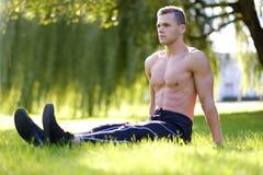 做瑜伽的赤裸上身的健身男性在公园 库存照片