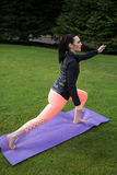 做瑜伽的运动妇女户外 免版税库存图片