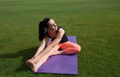 做瑜伽的运动妇女户外 免版税库存照片