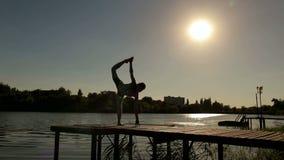 做瑜伽的运动的女孩剪影在小湖 股票录像