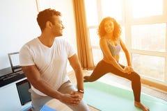 做瑜伽的非裔美国人的夫妇在家行使 他们在瑜伽席子的地板上站立 免版税图库摄影