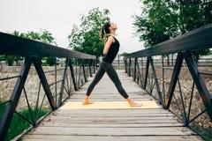 做瑜伽的年轻亭亭玉立的妇女 免版税库存图片