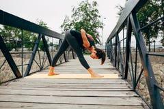 做瑜伽的年轻亭亭玉立的妇女 免版税库存照片
