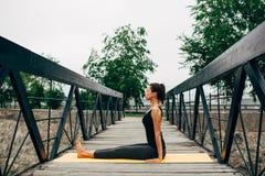 做瑜伽的年轻亭亭玉立的妇女 免版税图库摄影