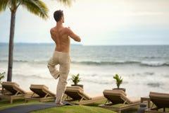 做瑜伽的年轻人在从后面的海滩行使 免版税库存照片