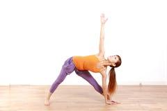 做瑜伽的年轻日本妇女扩大了三角姿势 图库摄影