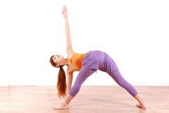 做瑜伽的年轻日本妇女旋转了三角姿势 库存图片