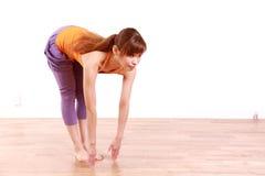 做瑜伽的年轻日本妇女站立向前弯姿势 库存照片