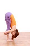 做瑜伽的年轻日本妇女站立向前弯 免版税库存图片