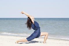 做瑜伽的年轻美丽的妇女在蓝色礼服的海边 免版税库存照片