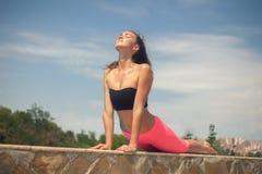 做瑜伽的年轻美丽的妇女室外晴天 免版税库存图片