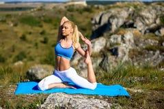 做瑜伽的年轻美丽的白肤金发的妇女在岩石行使 免版税库存照片