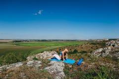 做瑜伽的年轻美丽的白肤金发的妇女在岩石行使 免版税图库摄影