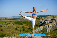 做瑜伽的年轻美丽的白肤金发的妇女在岩石行使 免版税库存图片
