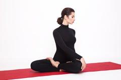 做瑜伽的黑衣服的美丽的运动女孩 莲花asana Padmasana姿势与左被解开的安置的 隔绝  免版税图库摄影