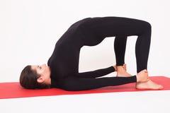 做瑜伽的黑衣服的美丽的运动女孩 Ardha chakrasana -半桥梁 背景查出的白色 免版税库存照片
