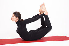 做瑜伽的黑衣服的美丽的运动女孩 Dhanurasana asana -摆在一把弓 背景查出的白色 免版税库存照片