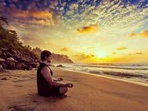 做瑜伽的年轻运动的适合人思考在热带海滩 免版税库存照片