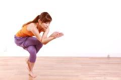 做瑜伽老鹰姿势的年轻日本妇女 库存照片