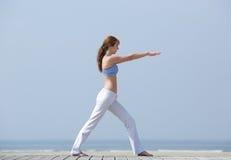 做瑜伽舒展的妇女在海滩 免版税图库摄影