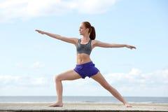 做瑜伽舒展的少妇在海滩 免版税库存照片