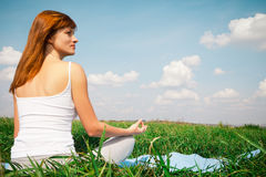 做瑜伽莲花姿势的女孩在公园 免版税库存图片