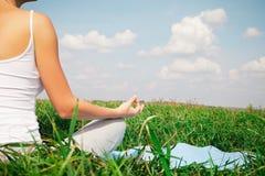做瑜伽莲花姿势的女孩在公园 库存图片