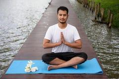 做瑜伽莲花岗位的亚裔人 库存图片