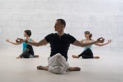 做瑜伽视图的男性教练员对砖墙 库存图片