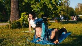 做瑜伽锻炼的两名年轻运动妇女在公园-一名妇女有长的蓝色dreadlocks 股票录像