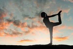 做瑜伽锻炼的女孩在日落 免版税库存照片