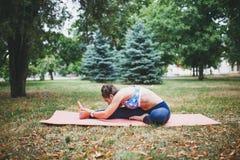 做瑜伽锻炼的女孩户外 图库摄影