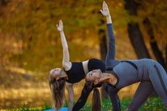 做瑜伽锻炼的接近的小组年轻女人在秋天城市公园 健康生活方式概念 免版税图库摄影