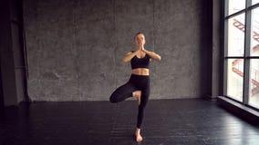 做瑜伽锻炼的白种人女孩 运动女子瑜伽训练 年轻亭亭玉立的运动的女孩握她的手  股票录像
